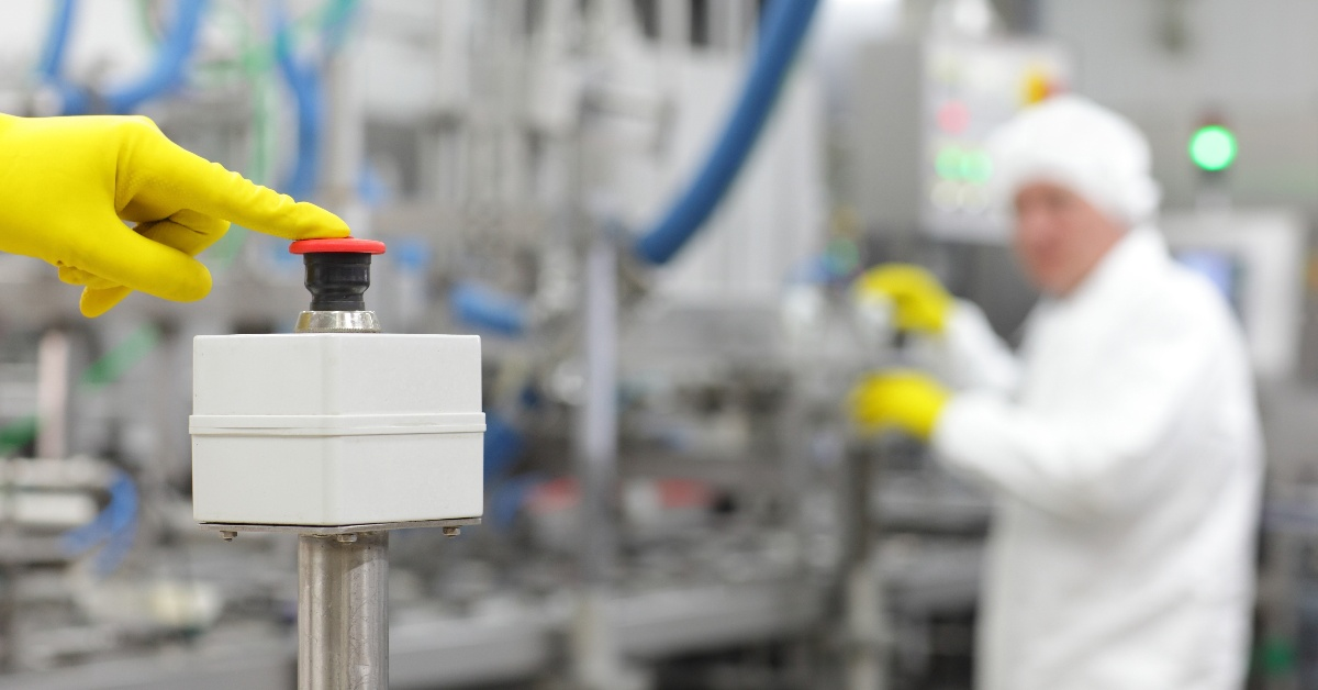 GMP operator pressing e-stop button on pharmaceutical processing equipment