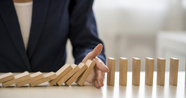 hand-blocking-falling-dominoes-as-risk-management